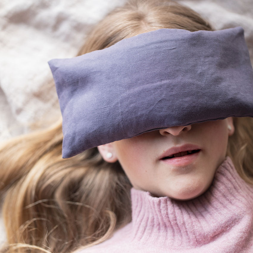 Woman using a relaxing lavender eye pillow from My Hand In Yours to help promote sleep