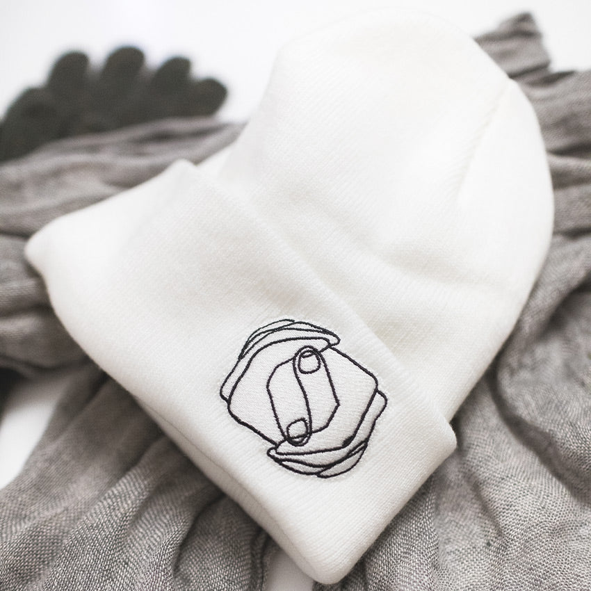 MHIY™ White Fleece-Lined Winter Beanie pictured on top of a scarf and gloves – winter gifts that help you stay warm provided by My Hand In Yours