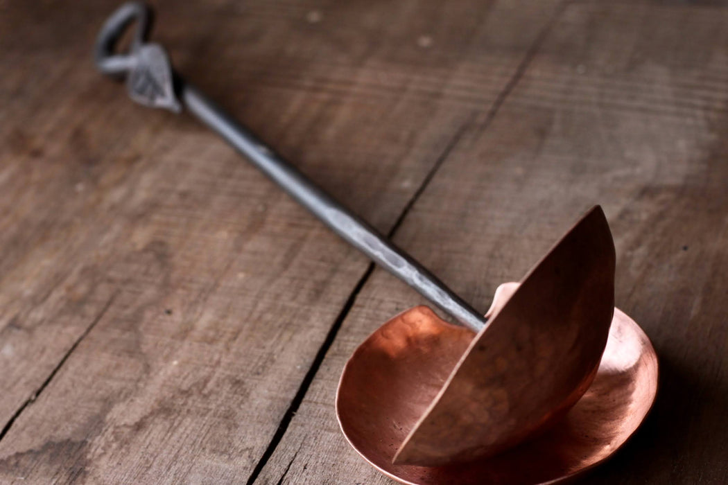 a blacksmith hand forged copper spoon rest under a ladle by Wicks Forge