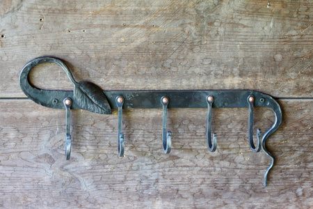 a blacksmith hand forged coat rack with and organic leaf and vine detail by Wicks Forge