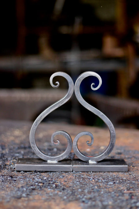a set of blacksmith hand forged bookends with a scroll design by Wicks Forge