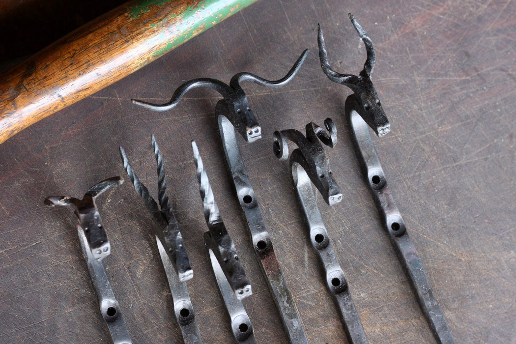 a collection of animal head hooks by Wicks Forge, including a Bull, Gazelle, Unicorn, Longhorn, Ram, and Antelope