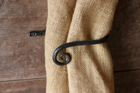 a blacksmith hand forged curtain holdback with a curl design by Wicks Forge