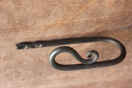 a blacksmith hand forged curtain holdback with a reverse curl design by Wicks Forge