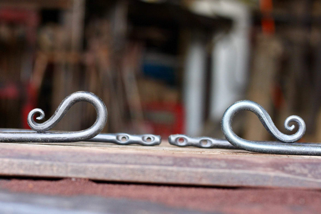 a set of blacksmith hand forged curtain holdback with a reverse curl design by Wicks Forge