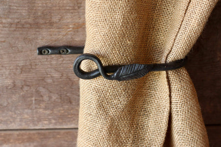 a blacksmith hand forged curtain holdback with a leaf design by Wicks Forge