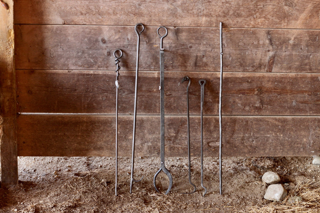 a collection of fire pokers and fireplace tongs by Wicks Forge