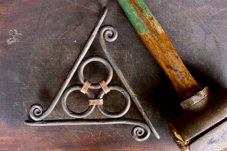 a blacksmith hand forged copper wrapped trivet with a fiddlehead detail by Wicks Forge