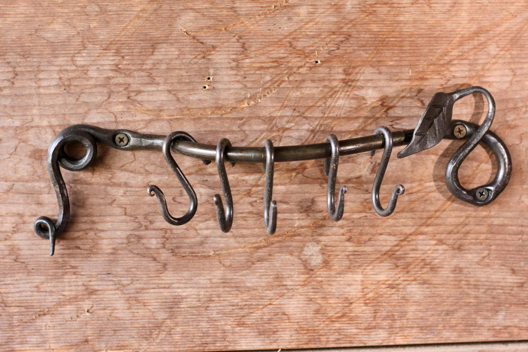 a blacksmith hand forged pot and pan rack with a leaf design by Wicks Forge