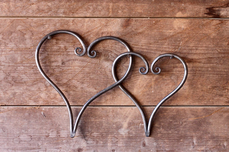 a pair of blacksmith hand forged linked hearts by Wicks Forge