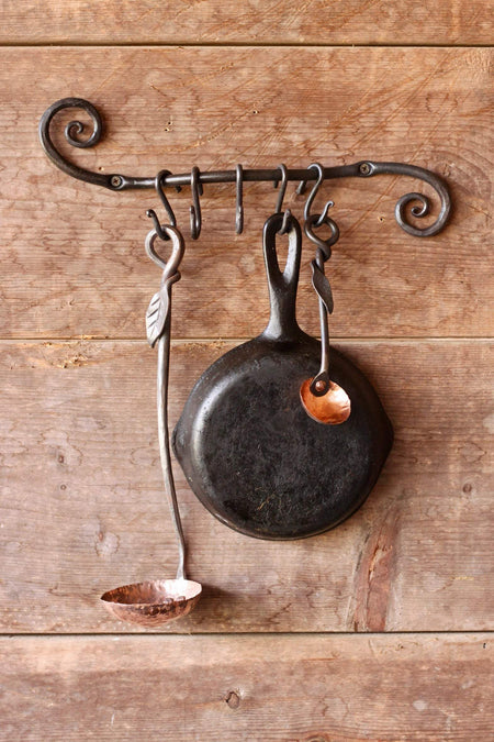 a blacksmith hand forged pot and pan holder with a scrolled design by Wicks Forge