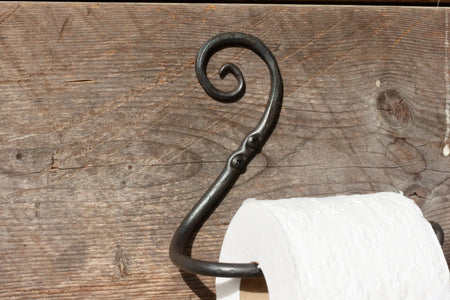 a blacksmith hand forged toilet paper holder with a curl detail by Wicks Forge