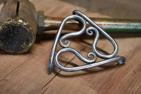 a blacksmith hand forged trivet pot holder by Wicks Forge