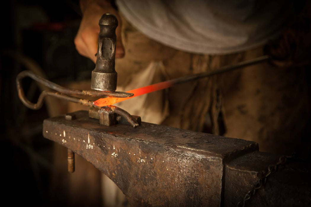 a blacksmith forging metal on an anvil