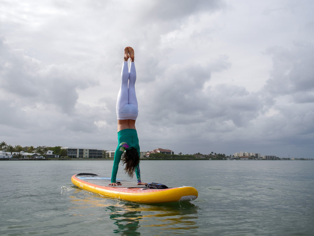 Girl doing handstand on an inflatable SUP