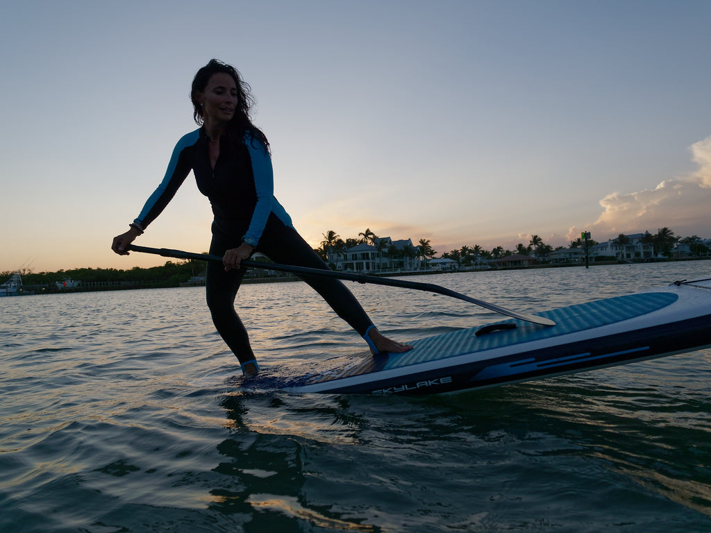 Girl doing a headstand on an inflatable SUP