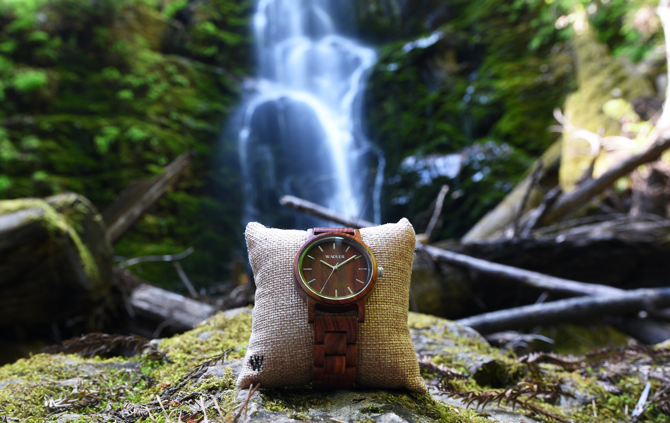 wooden watch in front of waterfall