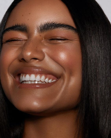 Woman smiling with glossy lips and glowing skin