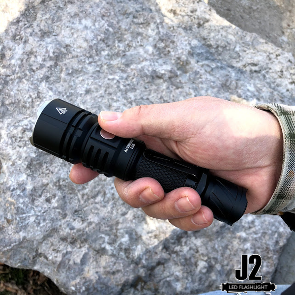 Holding an Acebeam L16 in one hand.