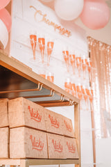 a wall of champagne accompanied by boxes of Vicky Bakery