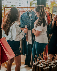 two young ladies with dark brown hair browsing a rack of clothes