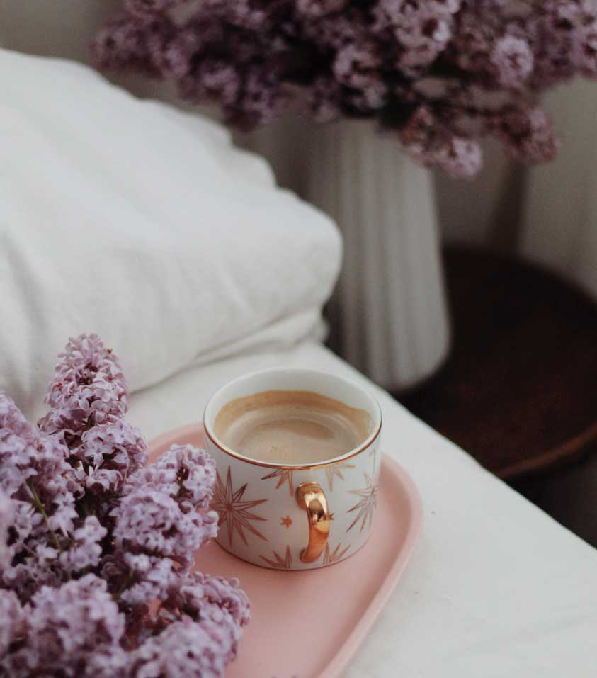White Bed with Romantic Lilac Flowers and Pink Tray