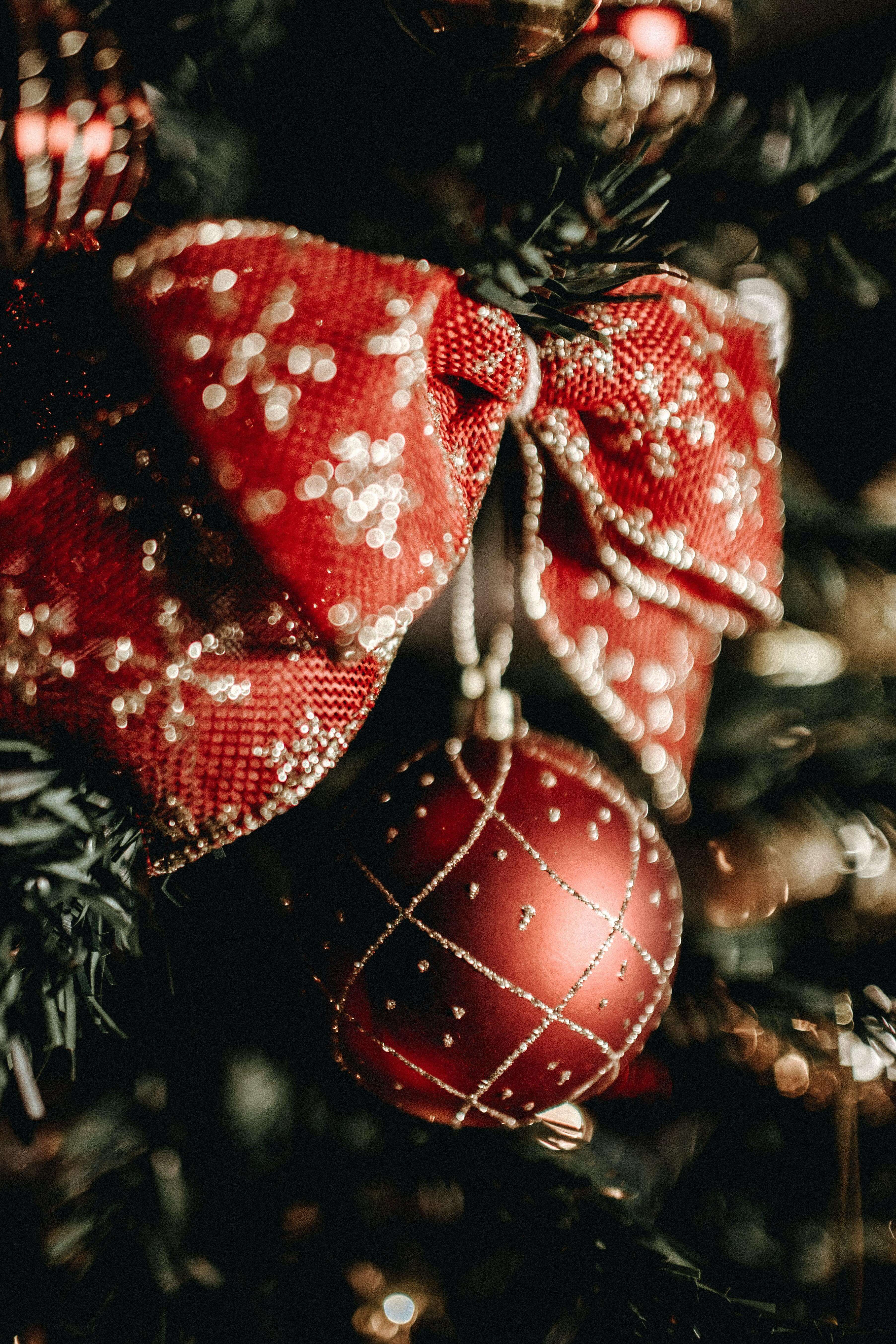 A close-up view of a red and white Christmas ornament and bow hanging on a tree