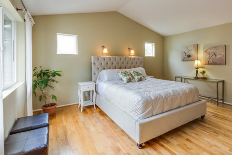 bedroom with hardwood floor and white upholstered bed
