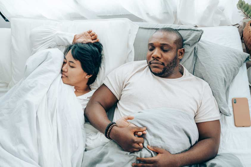 A couple sleeping in bed holding hands