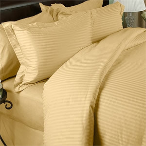A bed made with a gold sheet set