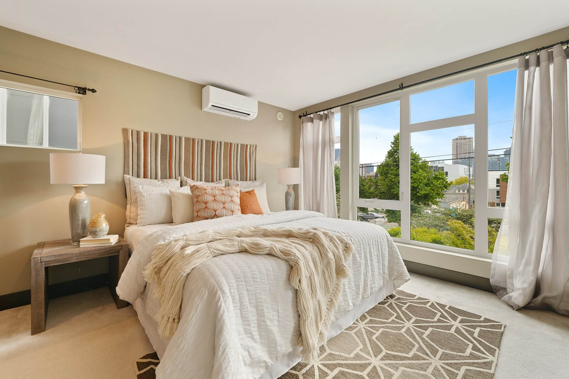 Bright summery bedroom with white bed set and large open windows