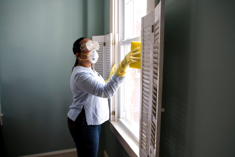 woman wearing face mask cleaning window