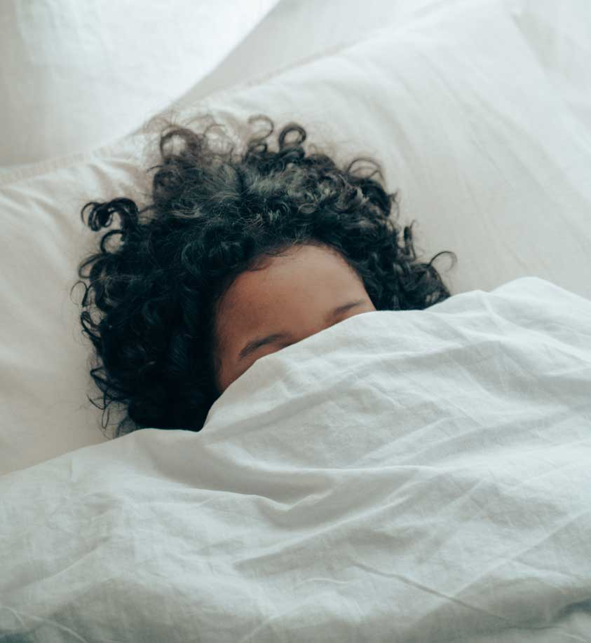 A woman sleeping with her face covered by a blanket.