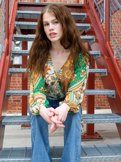 A long sleeve patchwork print top with a v neck, tie at the waist, and a row of diagonal buttons. The model is also wearing flare jeans.