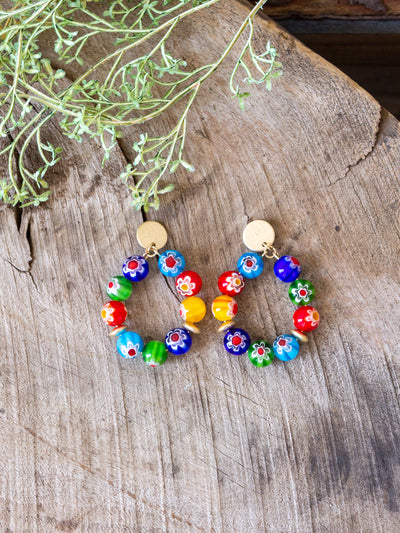 A pair of gold hoops with round colorful beads with flowers on them.