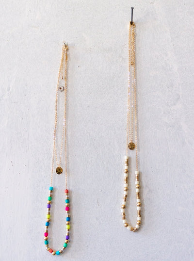 Two gold double layered necklaces. Both necklaces have a short layer with a gold disk and the second layer of one has colorful beads alternating with silver and gold beads. The second necklaces second layer is made of ivory and gold beads.