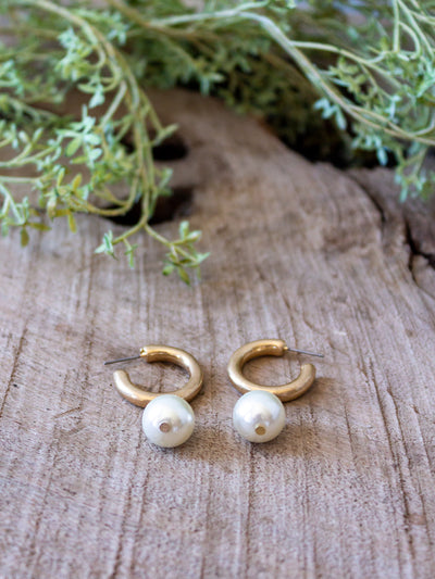A small gold hoop earring with a small pearl attached at the bottom.