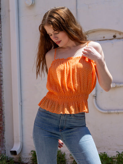 An orange peplum tank top with spaghetti straps and small white polka dots all over it. The model is wearing it with denim flare jeans.