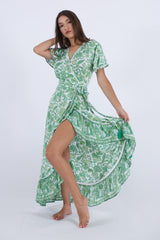 Model wearing our Palma long floral dress, with high low hemline in green floral pattern.