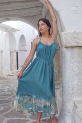 Model wearing an easy fitting blue long summer dress with open back and bottom frill.