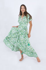 Our Palma high low summer dress, ties in the waist. It's in green color with a handprint floral pattern.