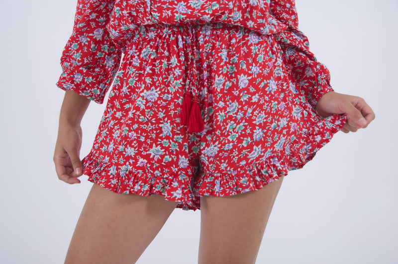 Detail of jumpsuit shorts with slight frill at the hemline , elastic waistband and tassel closure, in red floral pattern.