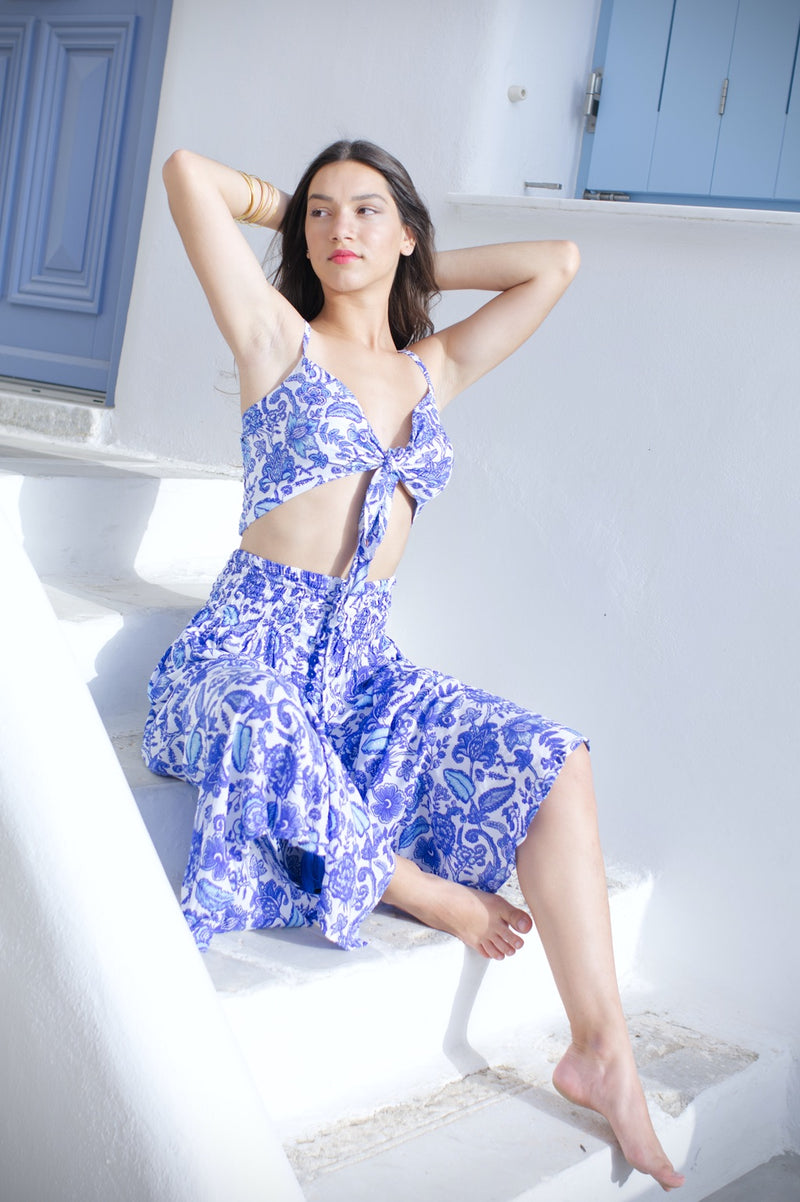 Image of model wearing a light summer skirt, in blue floral with matching crop top.