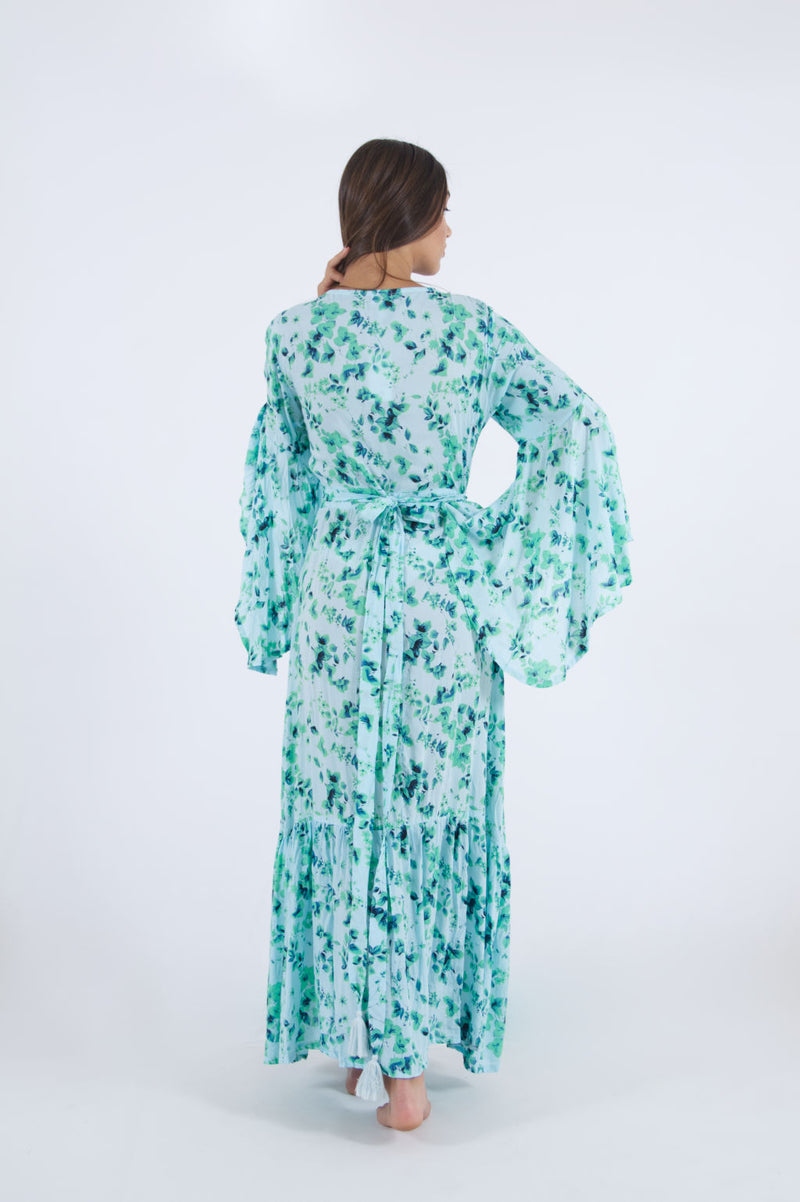 Image of model back side wearing our long wrap dress in floral pattern with bell sleeves.