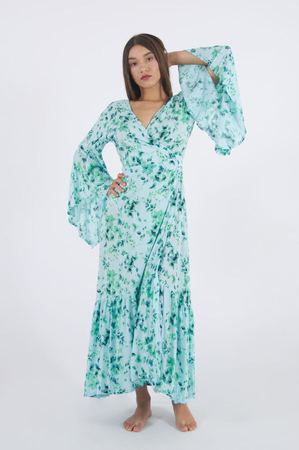 Model wearing our long floral dress with side wrap and trumpet sleeves.