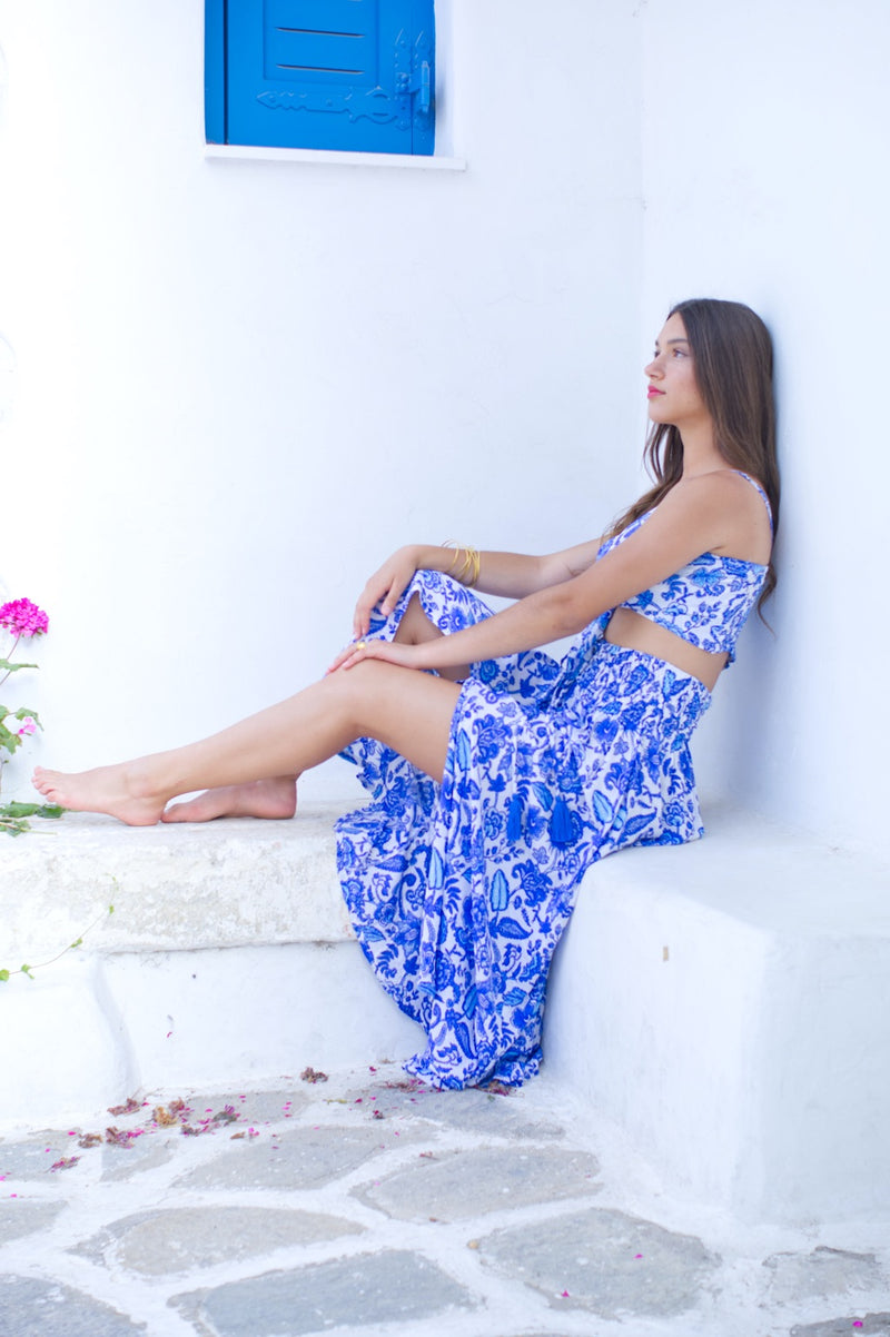 Our Agus long skirt outfit in handmade blue floral design. Image of model sitting.