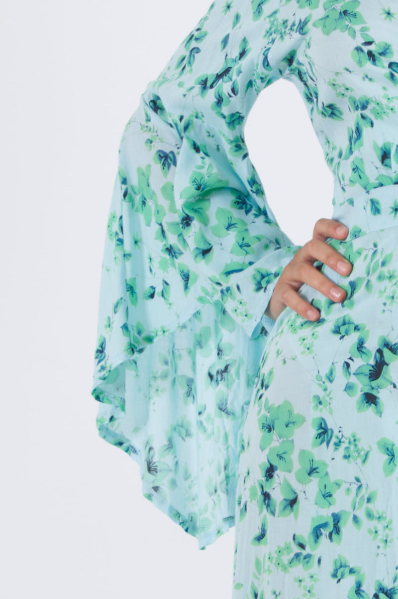 Detail of trumpet sleeve from our long wrap dress in green floral pattern.