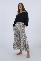 Image of summer outfit with animal print pants and black off shoulder top.
