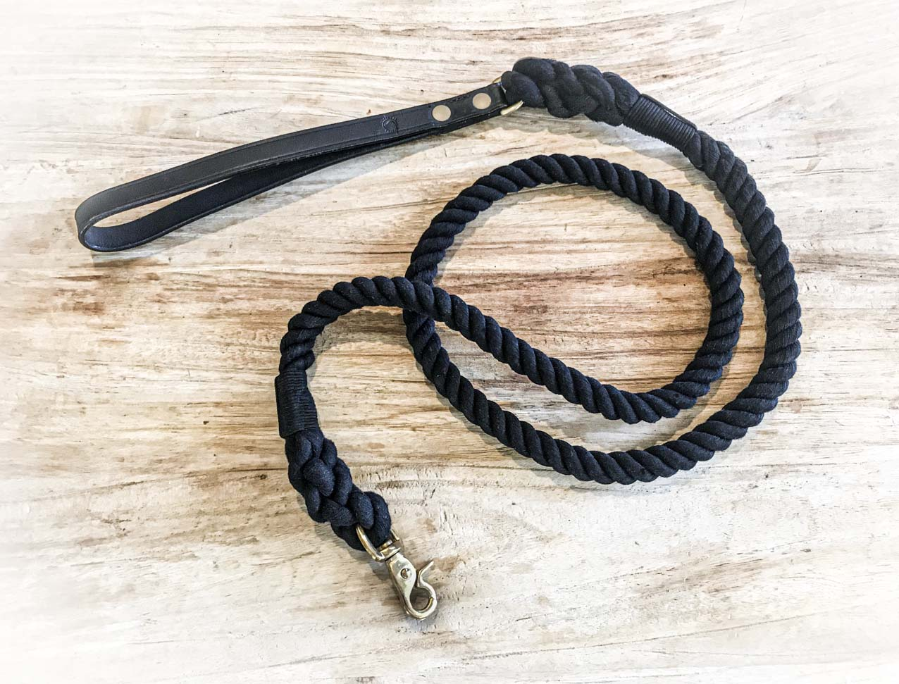 black rope dog lead laying on wood
