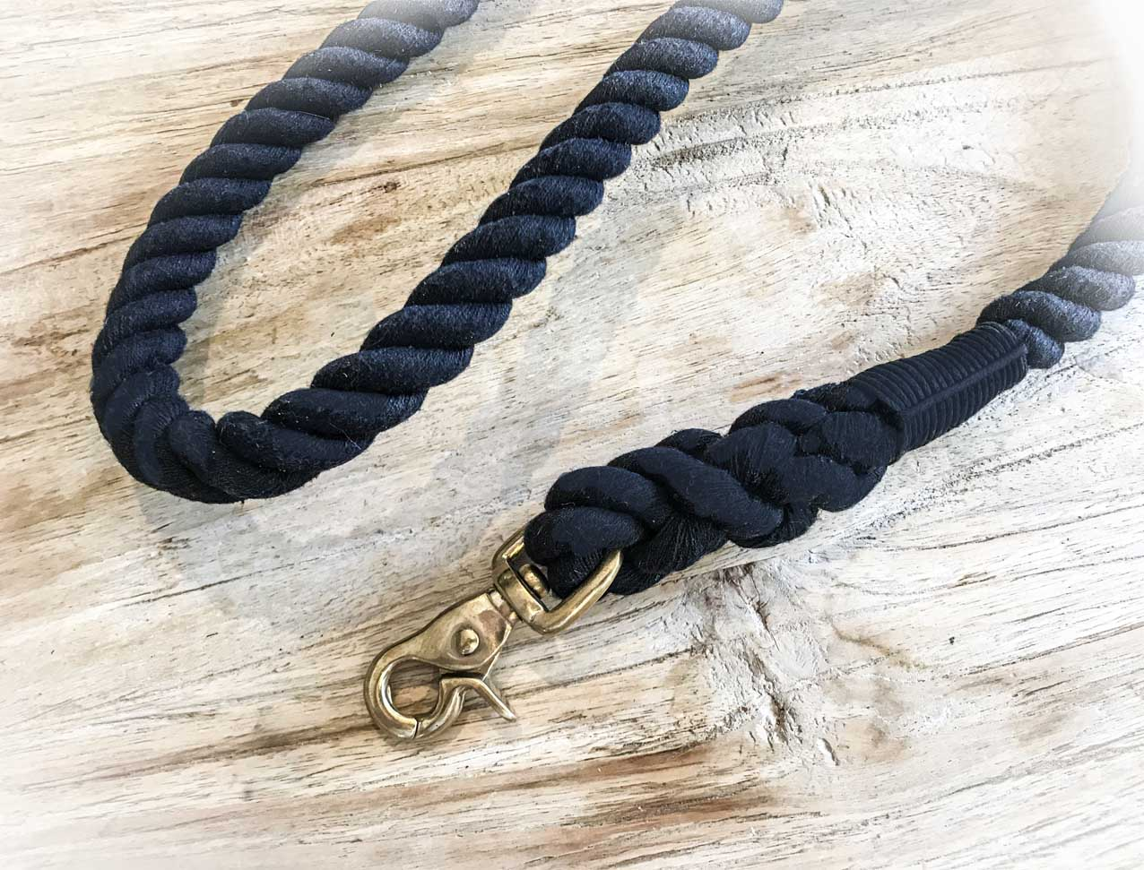 black rope dog lead with brass clip laying on timber